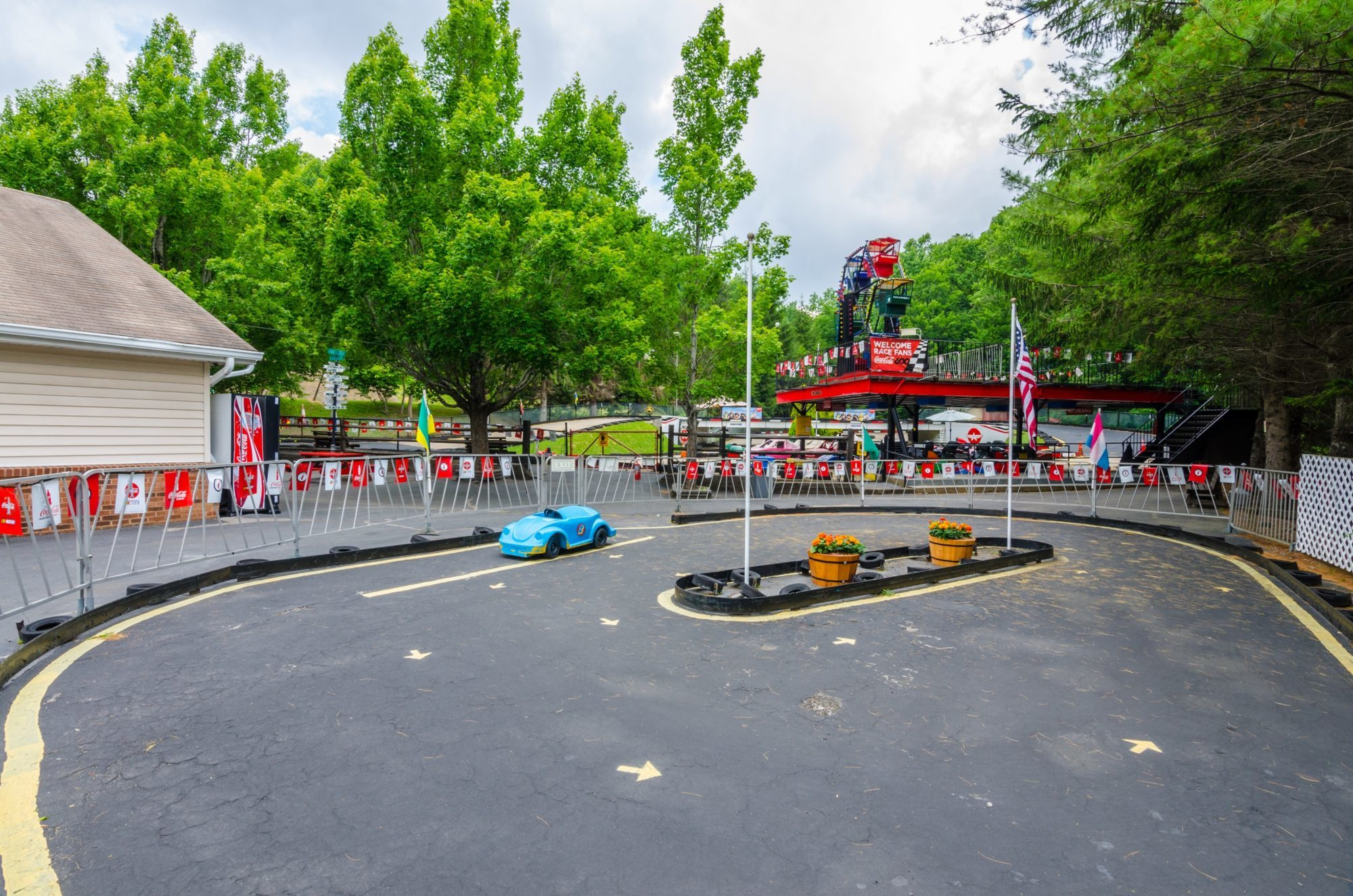 Car track with small pedal cars next to go kart track and wooden building with vending machine