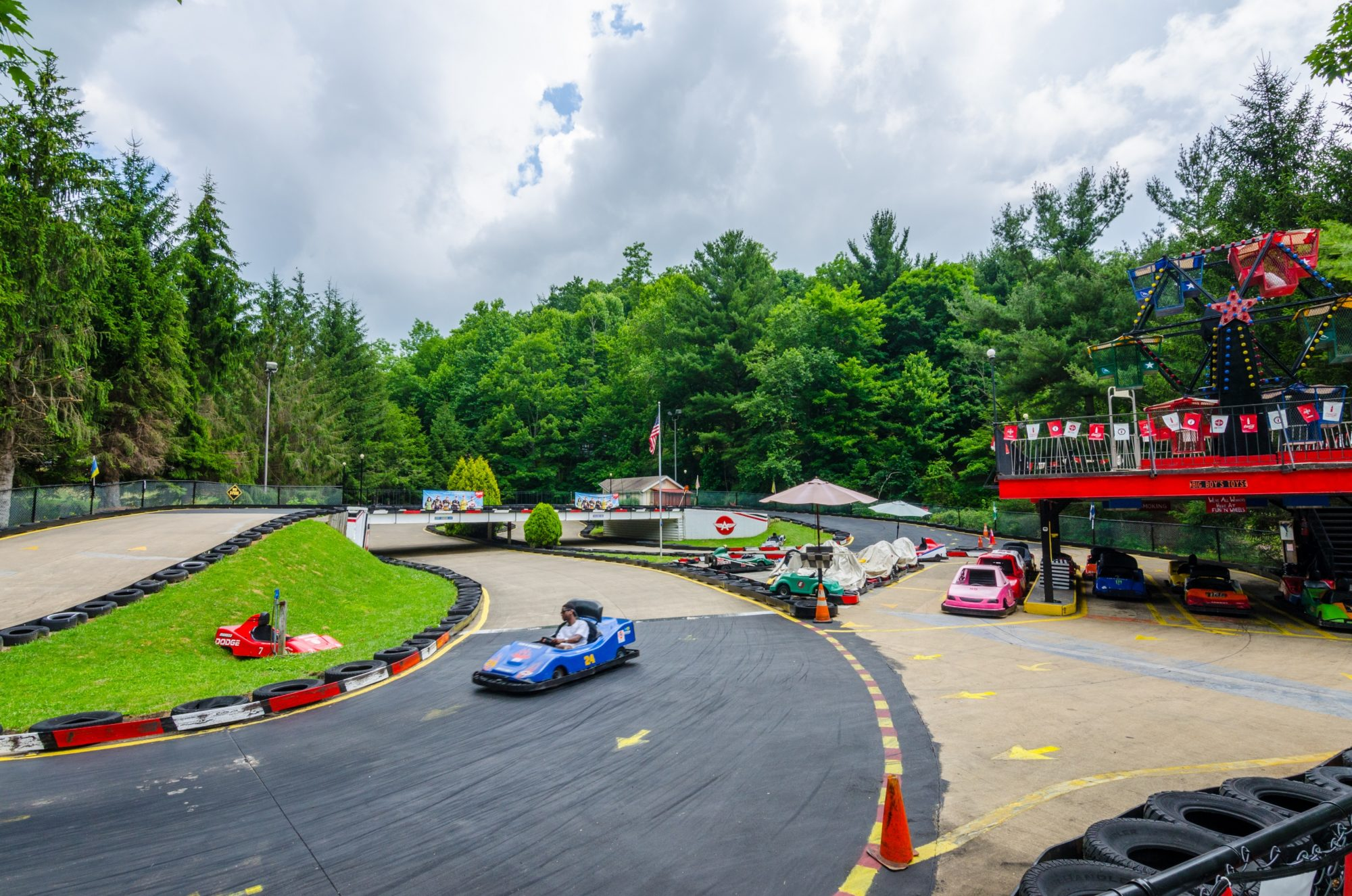 Go kart track surrounded by tall trees with go karts and small ferris wheel on raised area overlooking track
