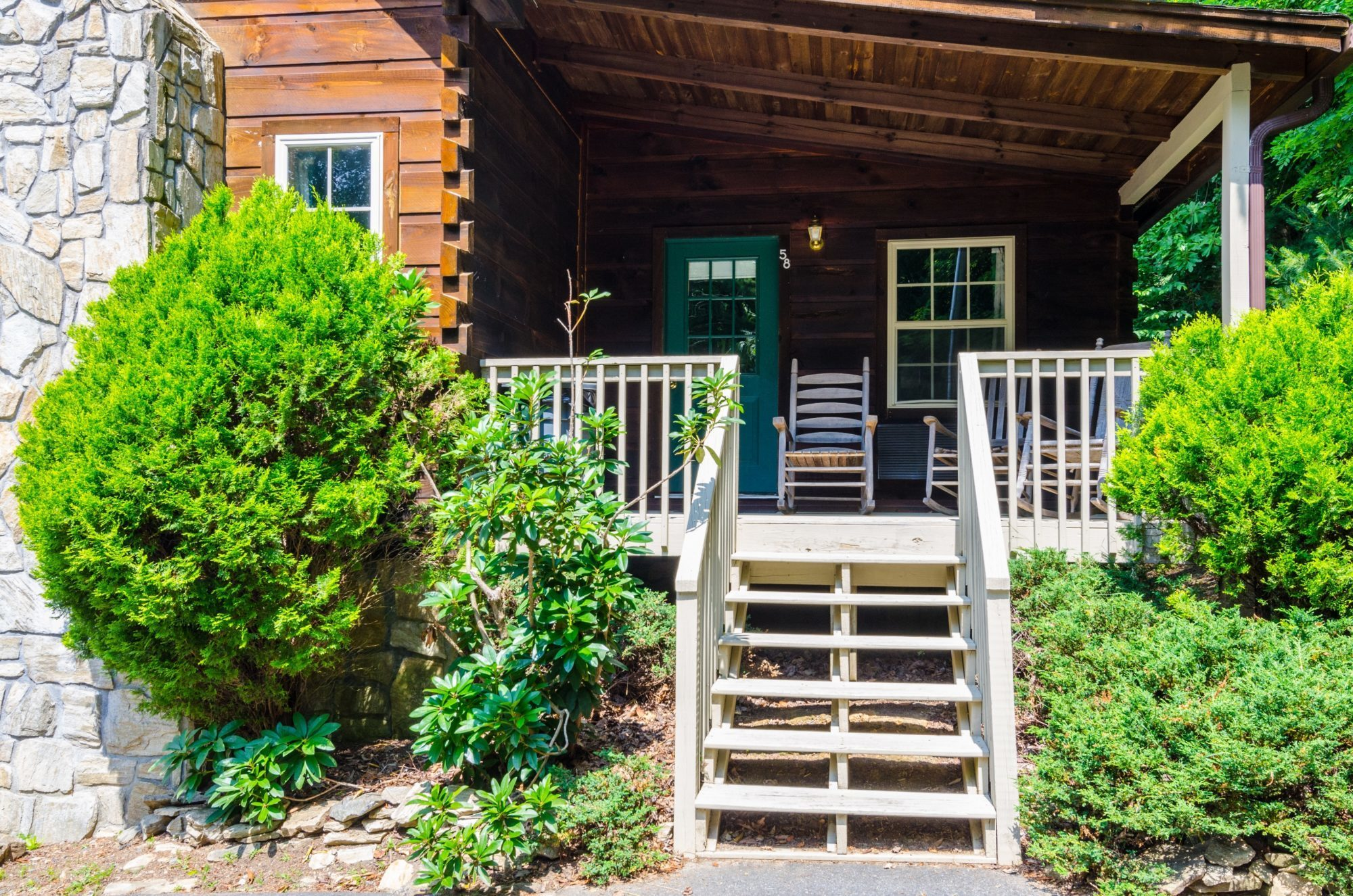 Cabin exterior showing wooden steps with small bushes leading to entrance door and porch area with rocking shairs