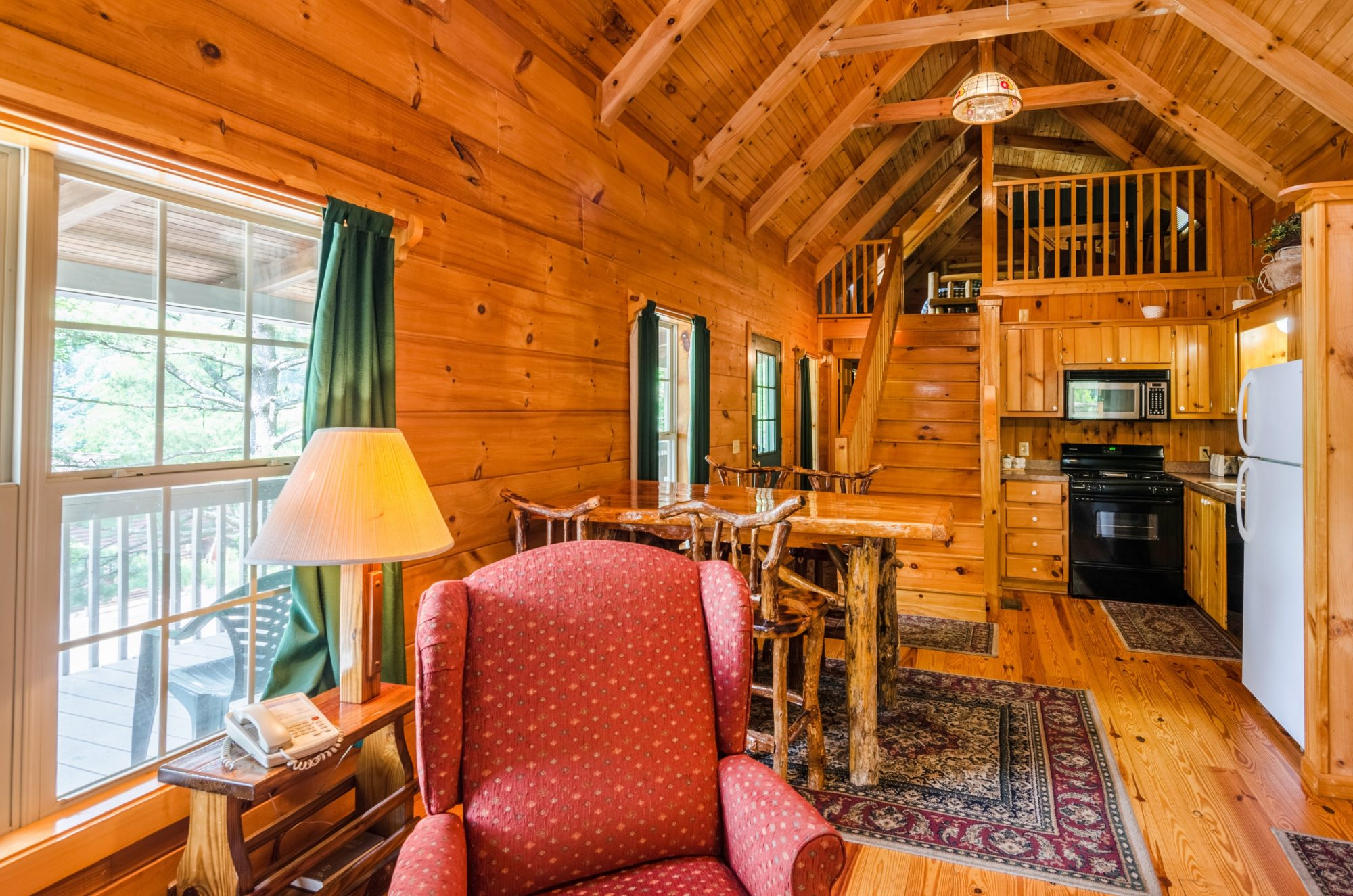 Wood panelled walls, wooden magazine rack with shelf and lamp, winged easy chair, entrance door in side hallway, wooden stairs leading to loft bedroom area, kitchen area with stove, microwave over stove, toaster, double sink, fridge freezer, wooden floor and large rugs