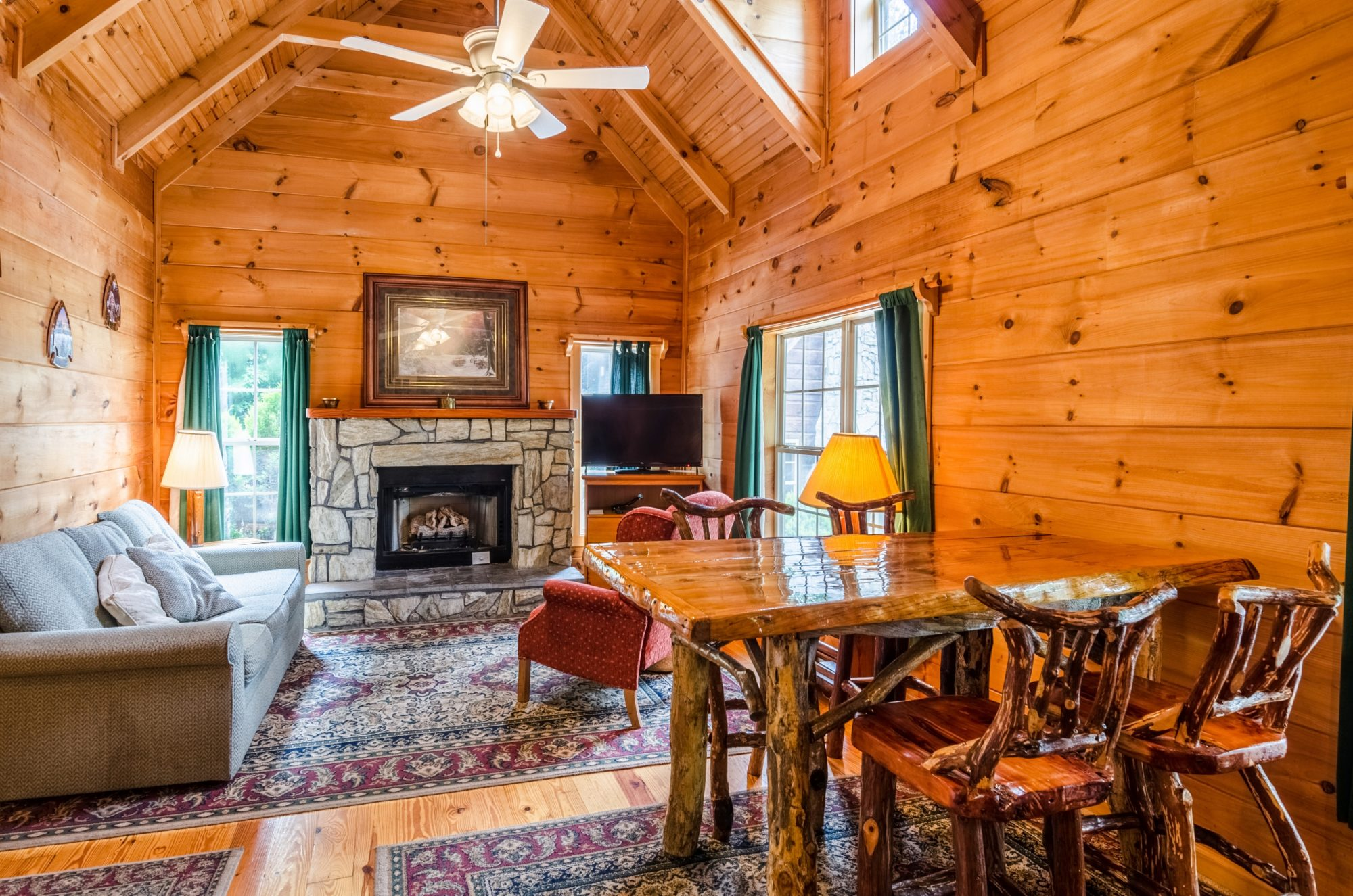 Wood panelled walls, sofa, side table with lam, fireplace with imitation logs, wall mounted art, corner unit with flat screen TV, rustic table and chairs, ceiling fan with light and wooden floors with large rugs