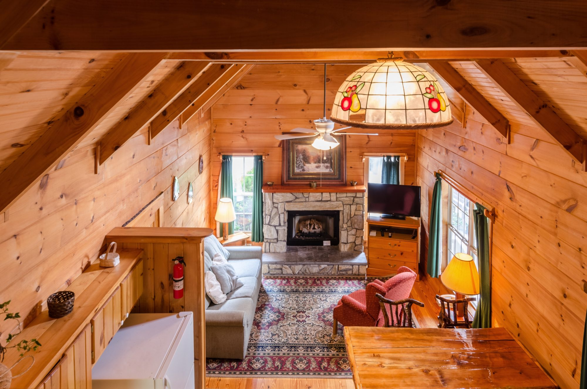 Cabin interior viewed from loft bedroom area with decorative ceiling lampshade and fire extinguisher looking down on sitting area with sofa, easy chair, side table with lap, fireplace, corner wooden storage unit with flat screen TV, wooden flooring with large rug