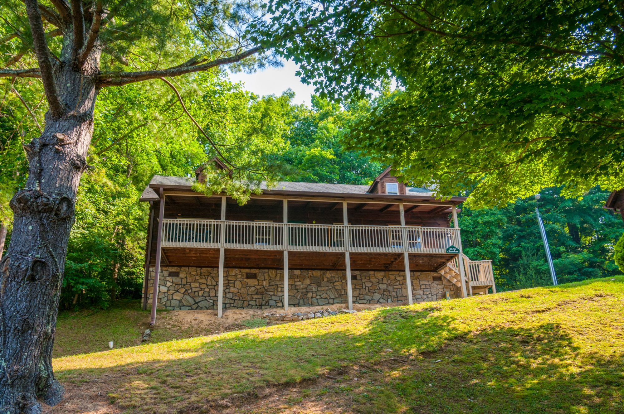 Cabin exterior showing wooden decking with wooden fencing, exterior wooden steps, trees, grassy area and landscaping