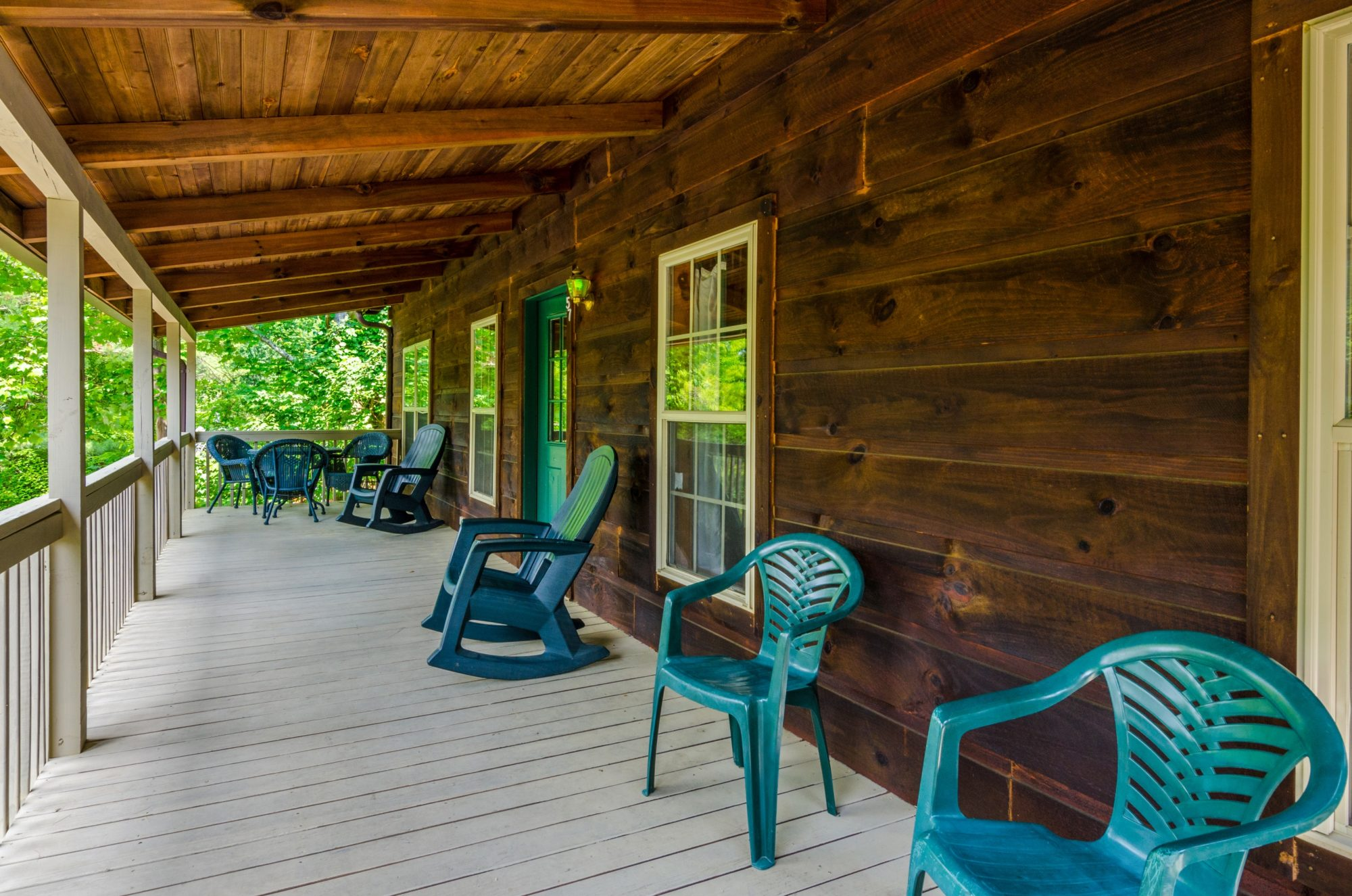 Tree shaded wooden porch with patio dining set, rocking chairs and extra chairs, cabin door and exterior light.