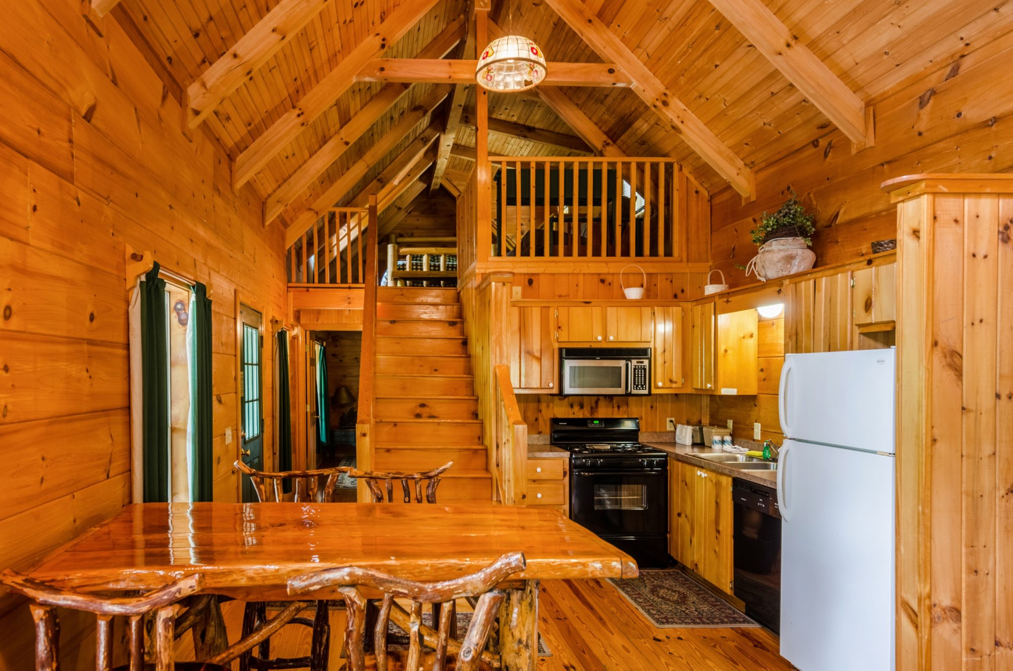 Rear door entrance with side hallway, rustic wooden tables and chairs, wooden stairs leading to a bedroom, kitchen area with stove, microwave over stovem wall and base cabinets, double sink, fridge freezer, wooden floor with rugs