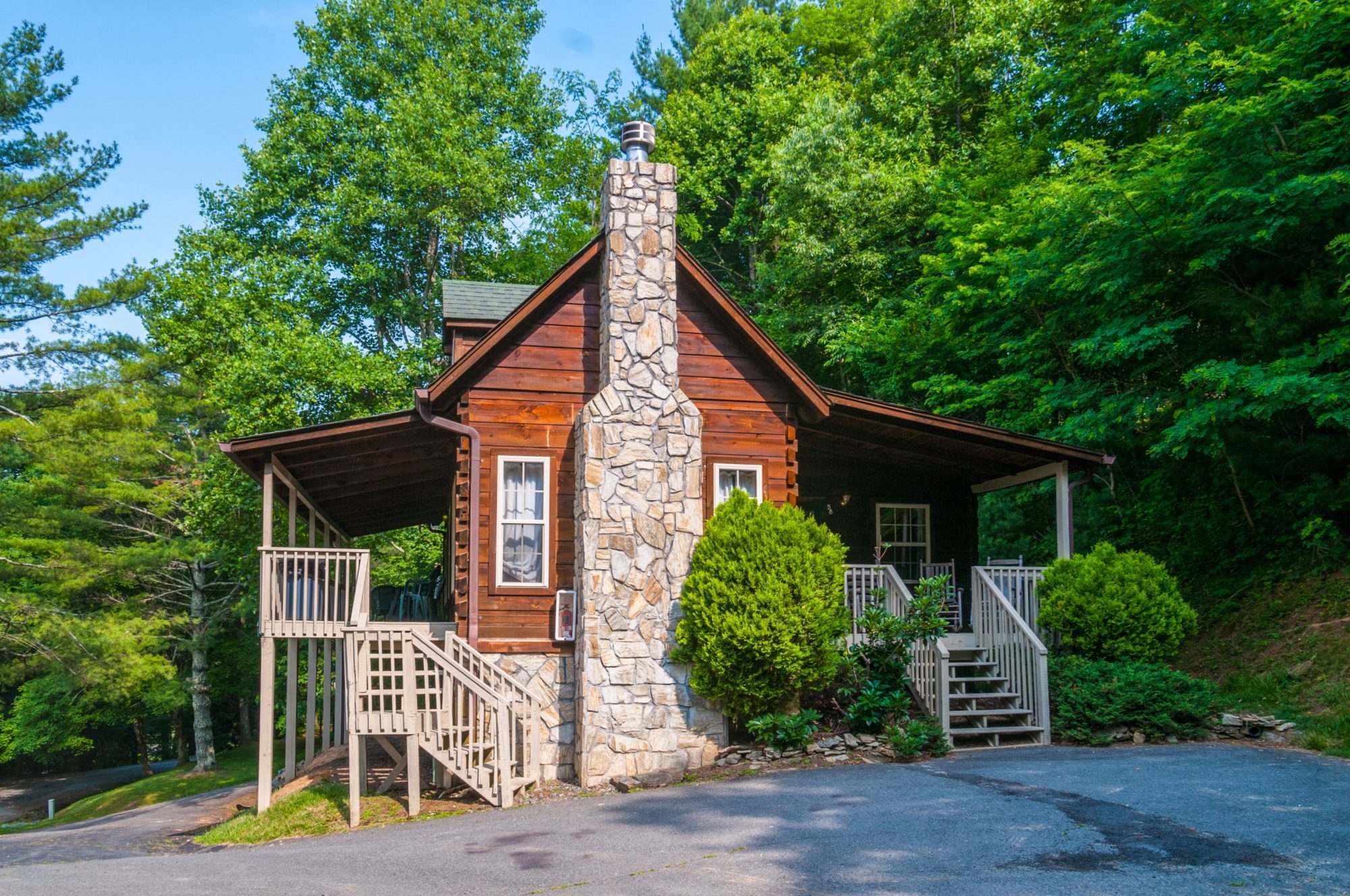 Cabin exterior showing wooden porch with rocking chairs and patio furniture, wooden steps, parking area, trees and landscaping busges
