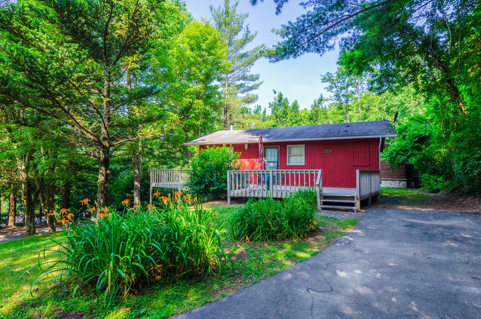 Red painted cottage exterior showing wooden deck with wooden railings, trees, landscaping and parking area