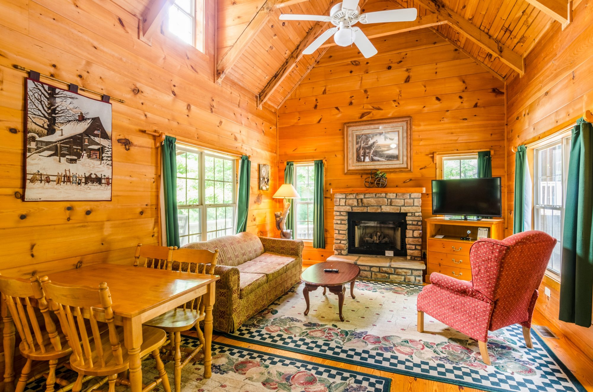 Wood interior with wooden table and chairs, sofa, wing easy chairs, coffee table, corner decorative floor lamp, fireplace with imitation log fire, corner storage unit with drawers and flat screen tv, wall mounted art, wooden floor with rugs