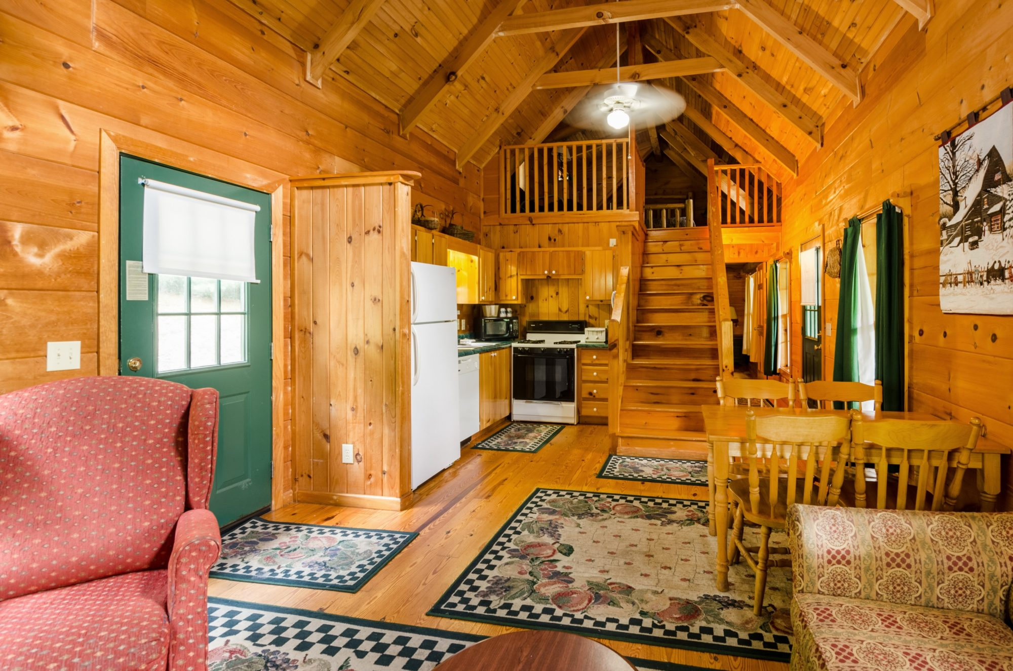 Cabin Front door, fridge, dishwasher, stove, microwave, microwave, table and chairs, sofa, wooden stairs leading to bedroom, side hallway with rear door and windows, wooden floor with rugs