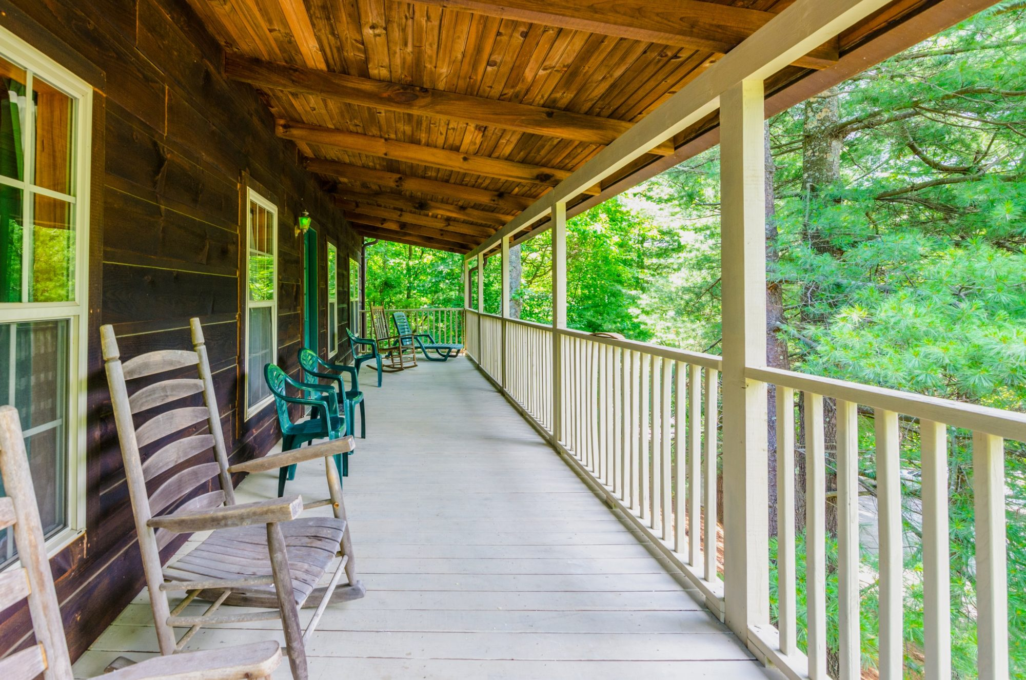 Wooden porch with wooden fencing, rocking chairs and patio furniture