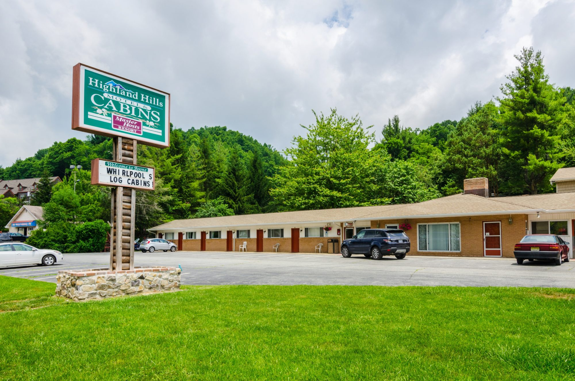 Motel exterior showing signage, motel rooms and parking area