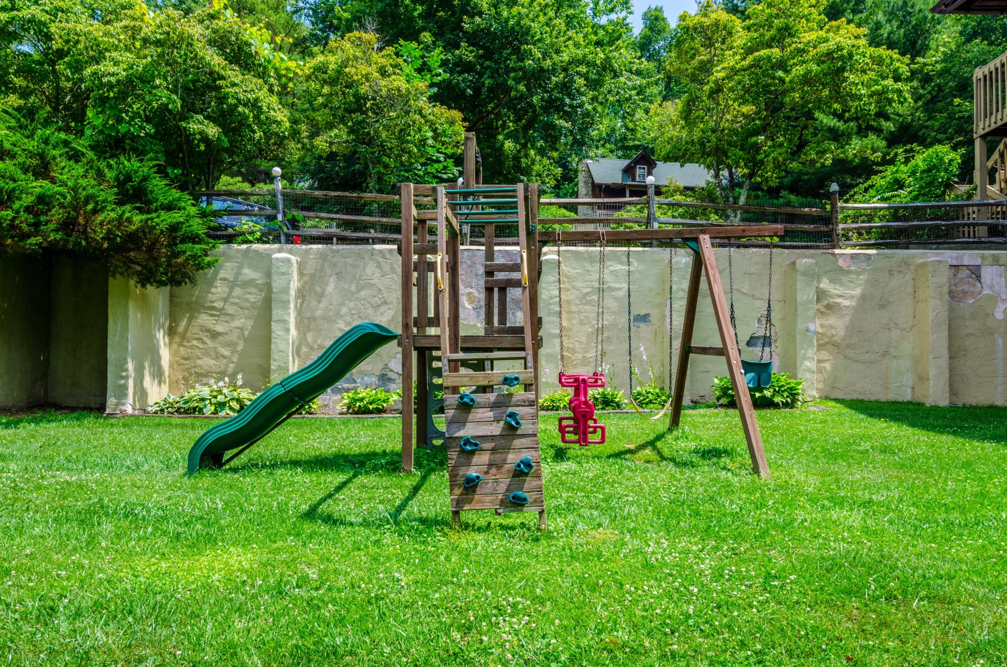 Children's activity set with slide, swings and climbing ramp set on grassy area with wall, wooden fencing and landscaping