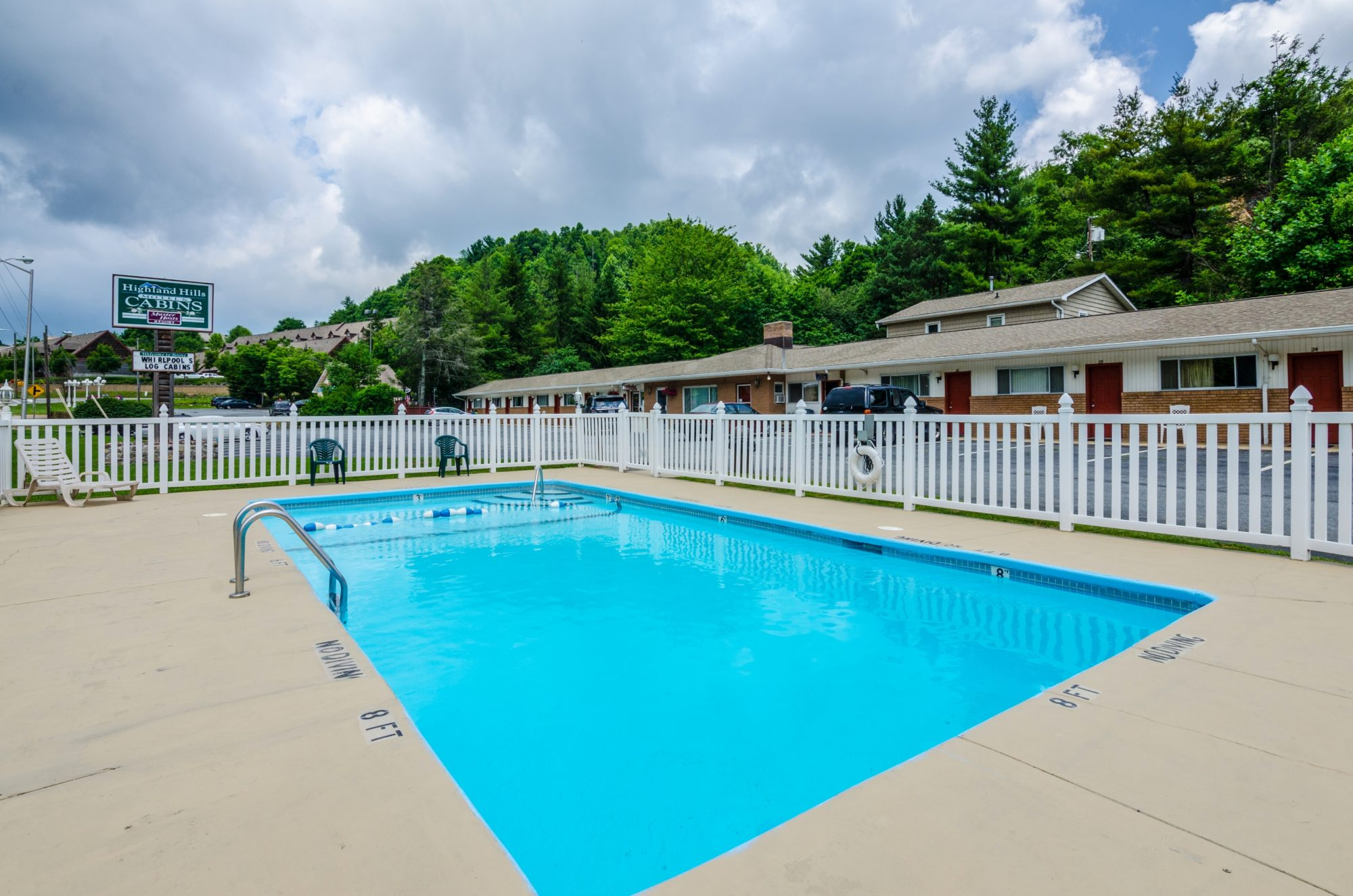 outdoor pool with concrete deck and patio furniture, white safety fencing and life saver, motel signage, motel rooms and parking area