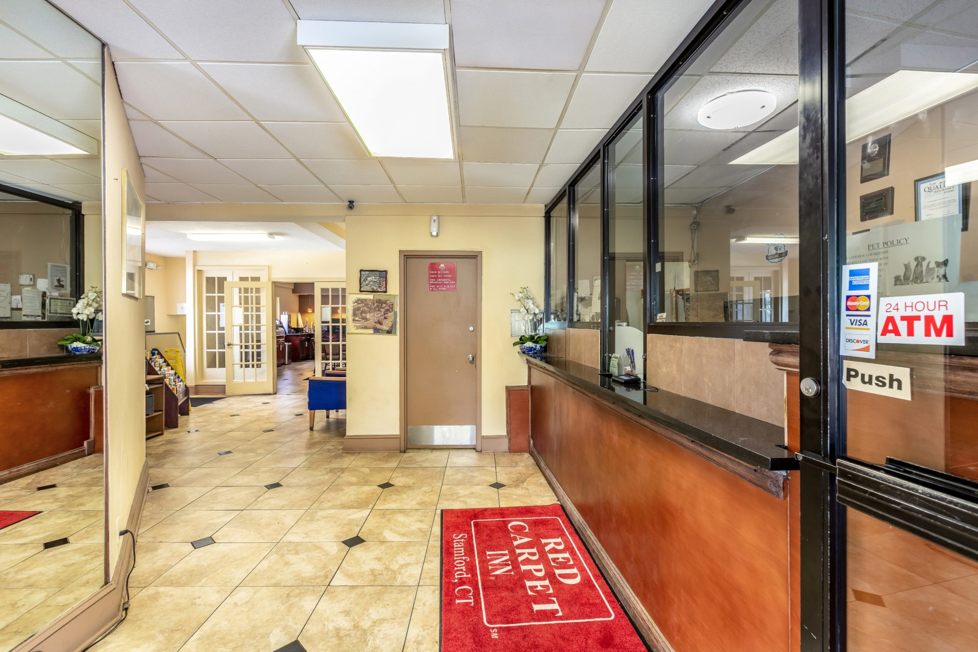 Reception desk, guest information leaflet stand, double doors leading to breakfast area and tiled flooring