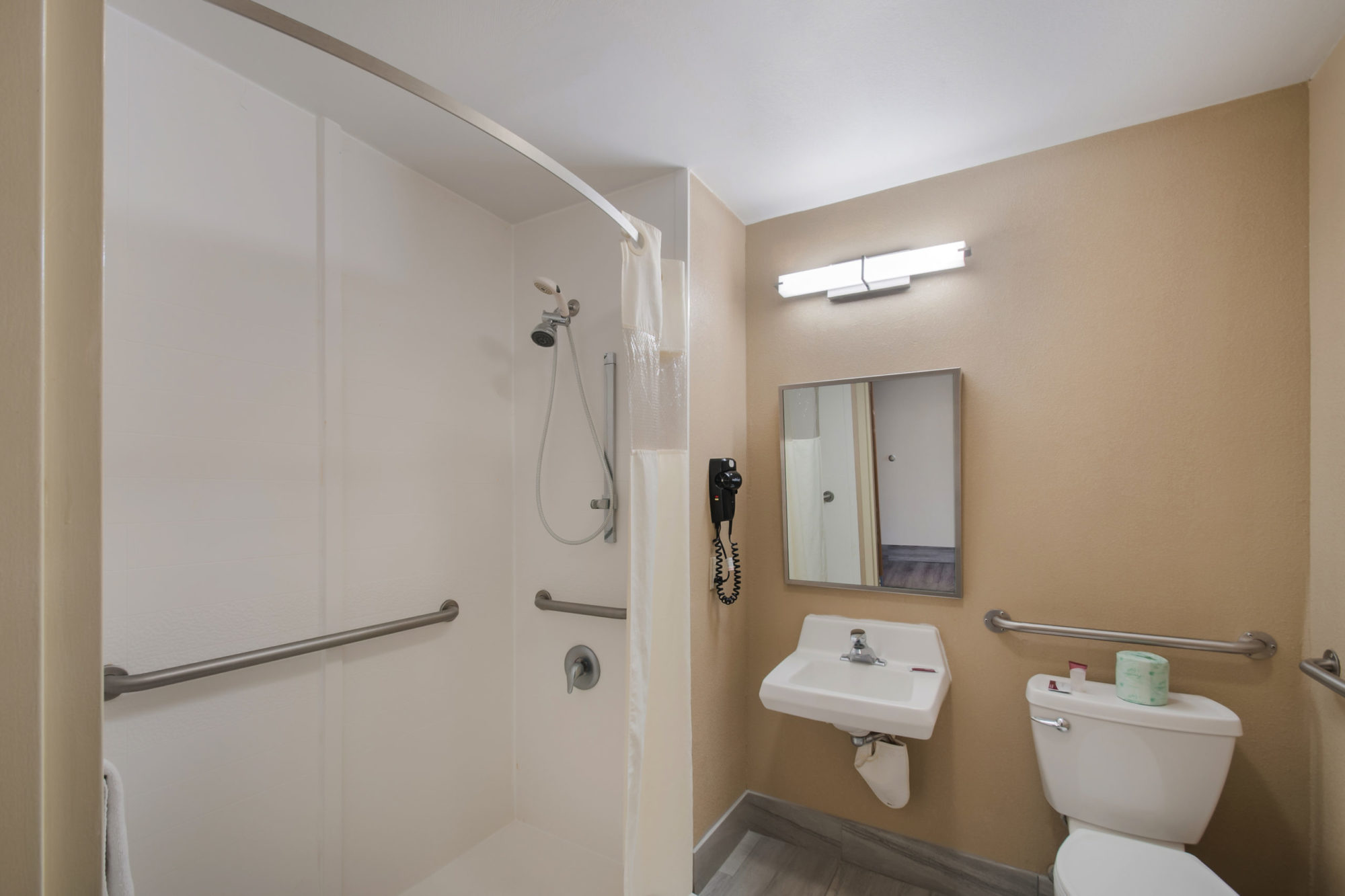 Shower Tub with grab handles and wall mounted towel rail with towel, sink, wall mounted mirroe with overhead strip light, wall mounted hair dryer, grab handles by toilet, bathroom amenities and tiled floor