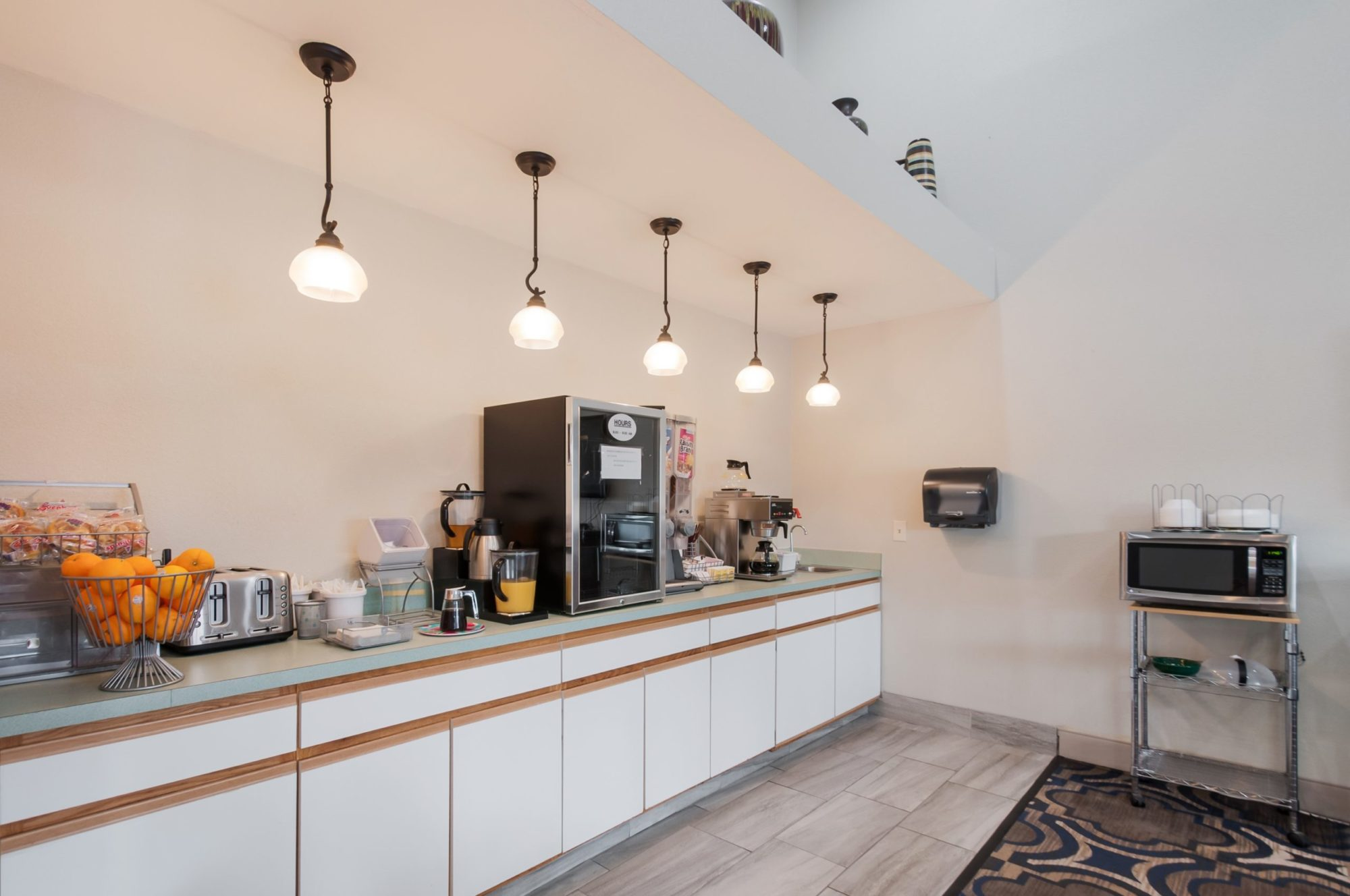 Breakfast counter with coffee machine, cereal dispenser, pitchers of juice, toaster, assorted breakfast pastries, fresh fruit , microwave, wall mounted paper towel dispenser, suspended lighting, disposable plates and silver ware, caarpet and tile flooring