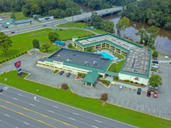 Drone view of hotel exterior, canopy hotel entrance,brand signage, parking spaces, two story building, outdoor pool, grassy areas, trees and small bushs, river with fishing desk