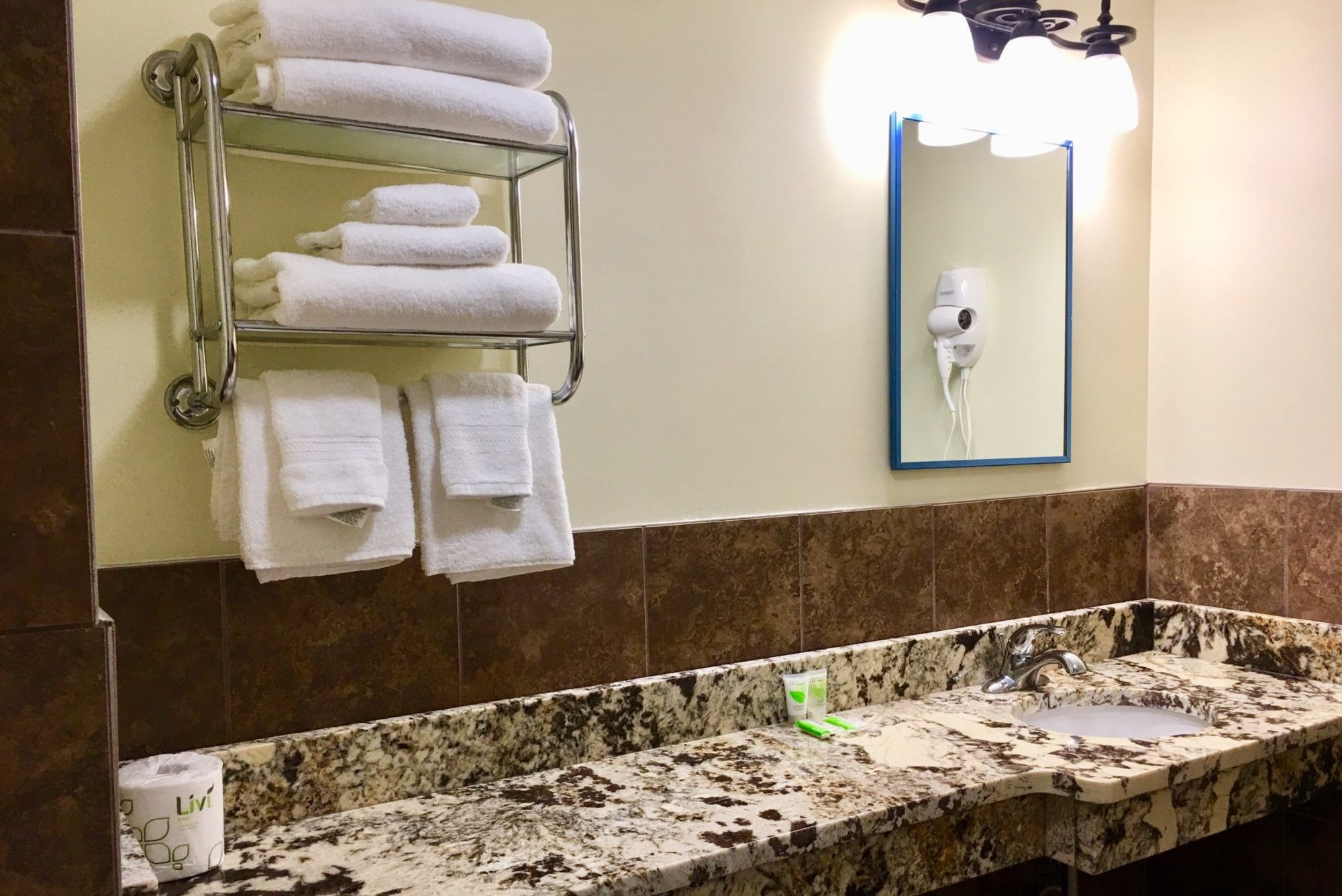 vanity unit, shelves with towels, mirror with overhead lights