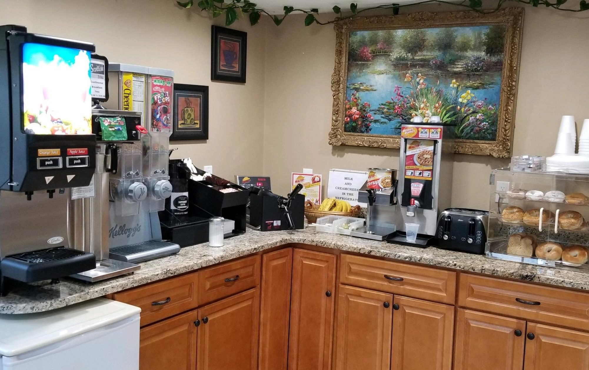 Breakfast display with juice dispenser, cereal dispensers, fruit, waffle machine, toaster, breakfast pastries display case