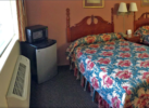 Two double beds, night stand with telephone, wall mounted bedside lights and art, fridge with microwave, carpet flooring