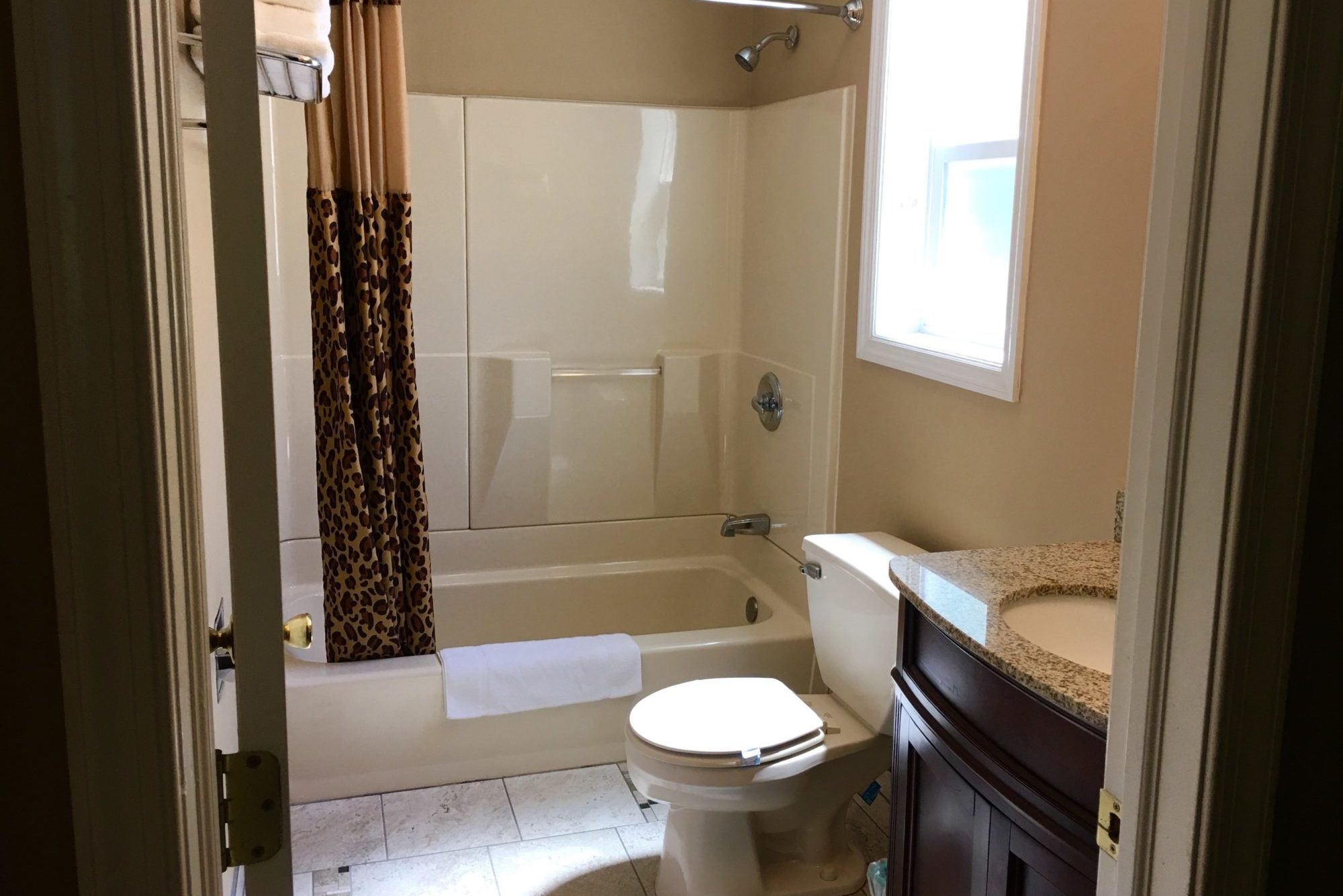 Shower tub with shower curtain, vanity unit, toilet, tiled flooring