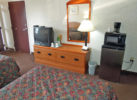 Two double beds, wooden unit with tv and lamp, wall mounted mirror, fridge with microwave, carpet flooring