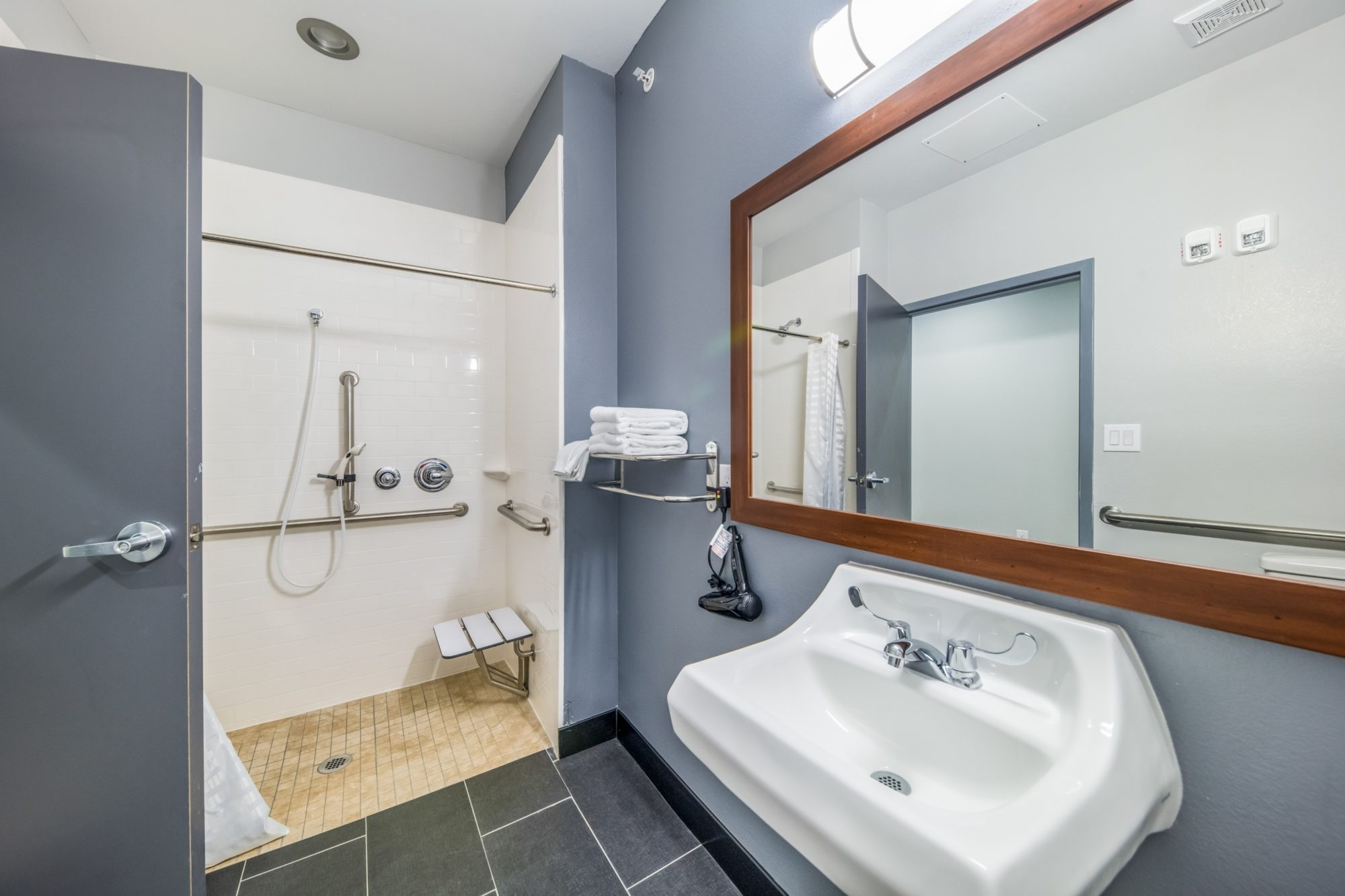 Walk in showwer, seat, grab bars, shower curtain, towel rail and shel with towels, mirror, hairdryer, sink, tiled flooring