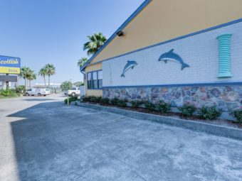 Brand signage, hotel entrance, palm trees, parking spaces