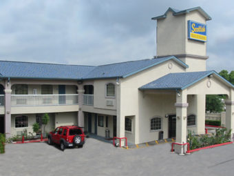 hotel entrance with drive through canopy, two story building with exterior room entrances, parking spaces