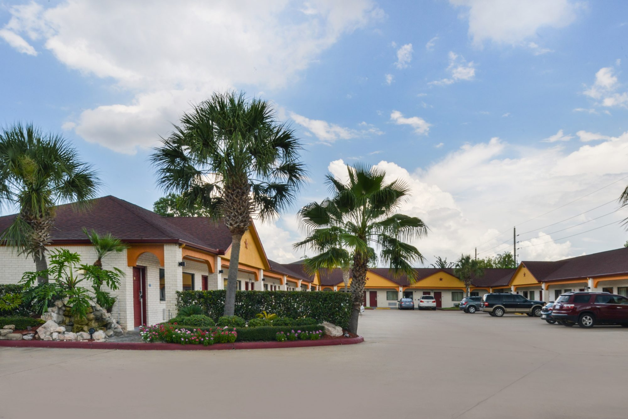 one story building with exterior room entrances, parking spaces, landscaping with trees, shrubs and flowers