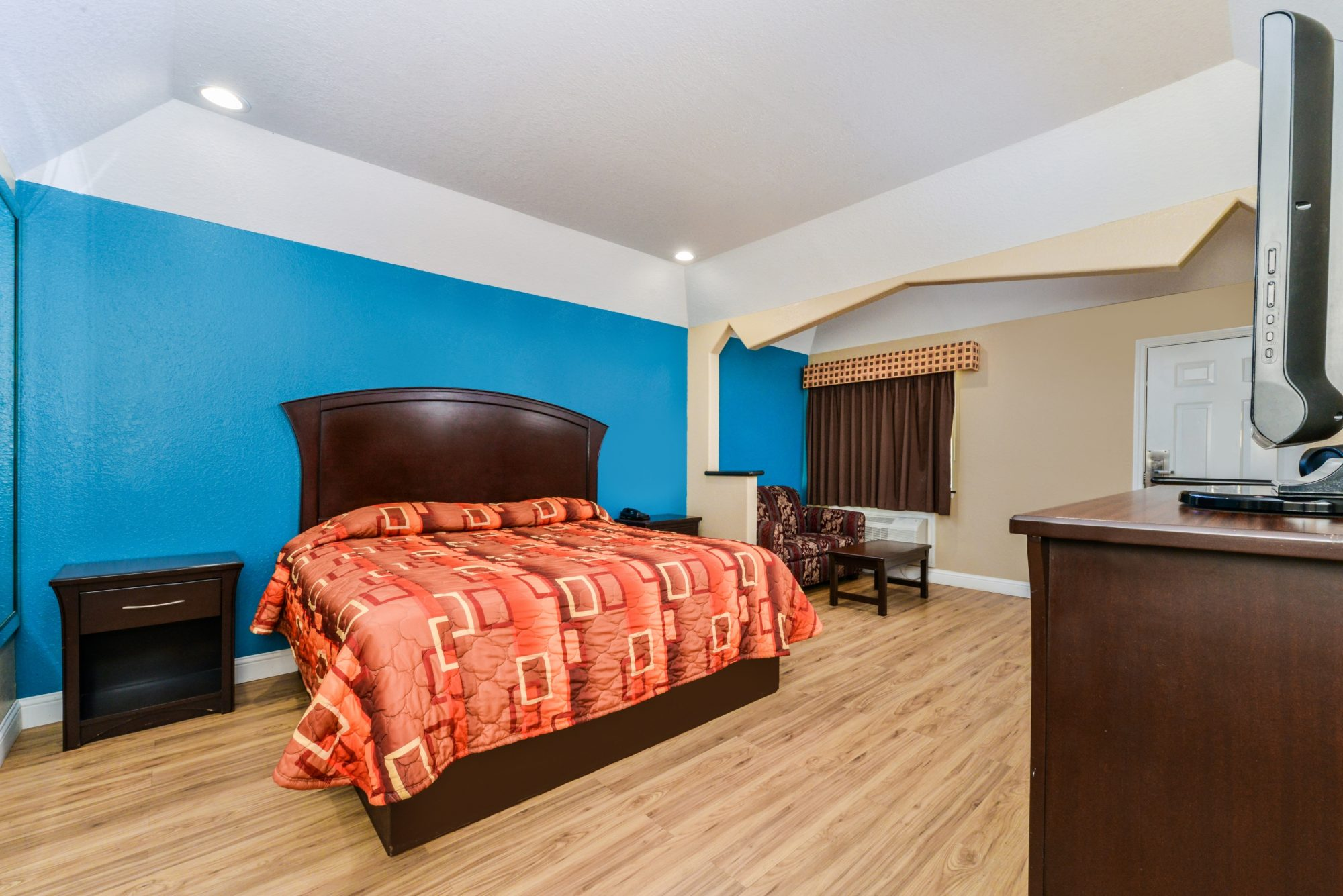 king bed, night stands with telephone, sofa, coffee table, wooden unit with flat screen tv, laminate flooring