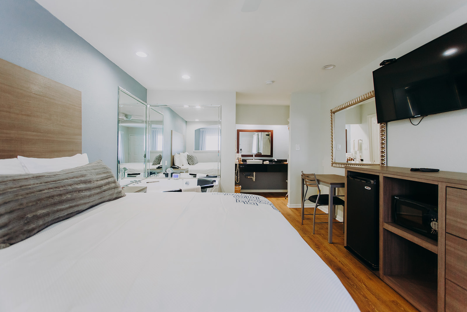 King bed, jacuzzi, mirrored walls, wooden unit with fridge and microwave, wall mounted flat screen tv, desk with chair, mirror, alcove with vanity unit and mirror, laminate flooring