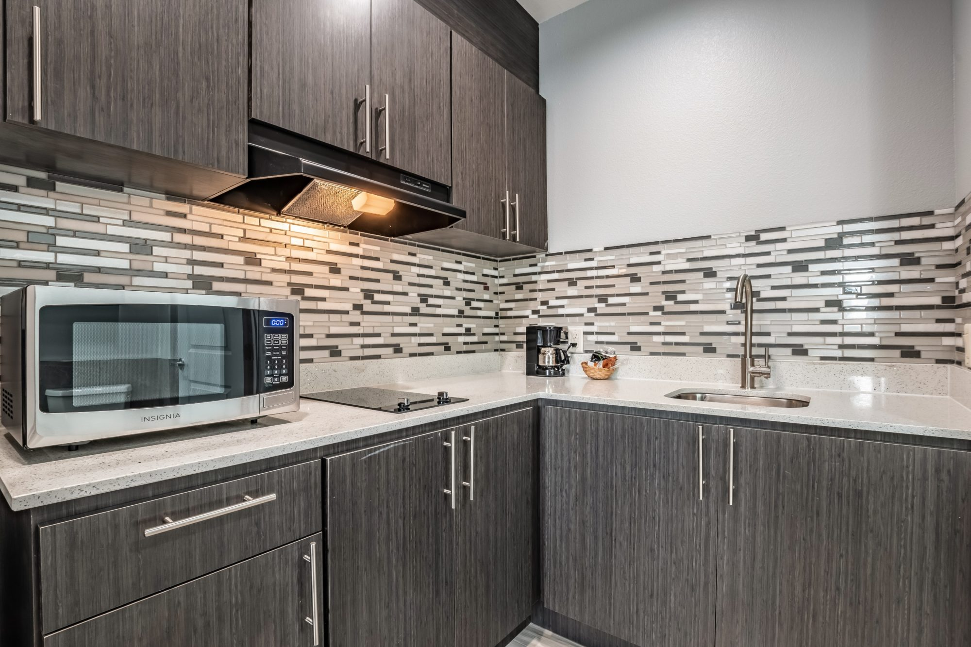 Wall and base cabinets with cooker hood, counter top with microwave, hob,coffee maker, sink