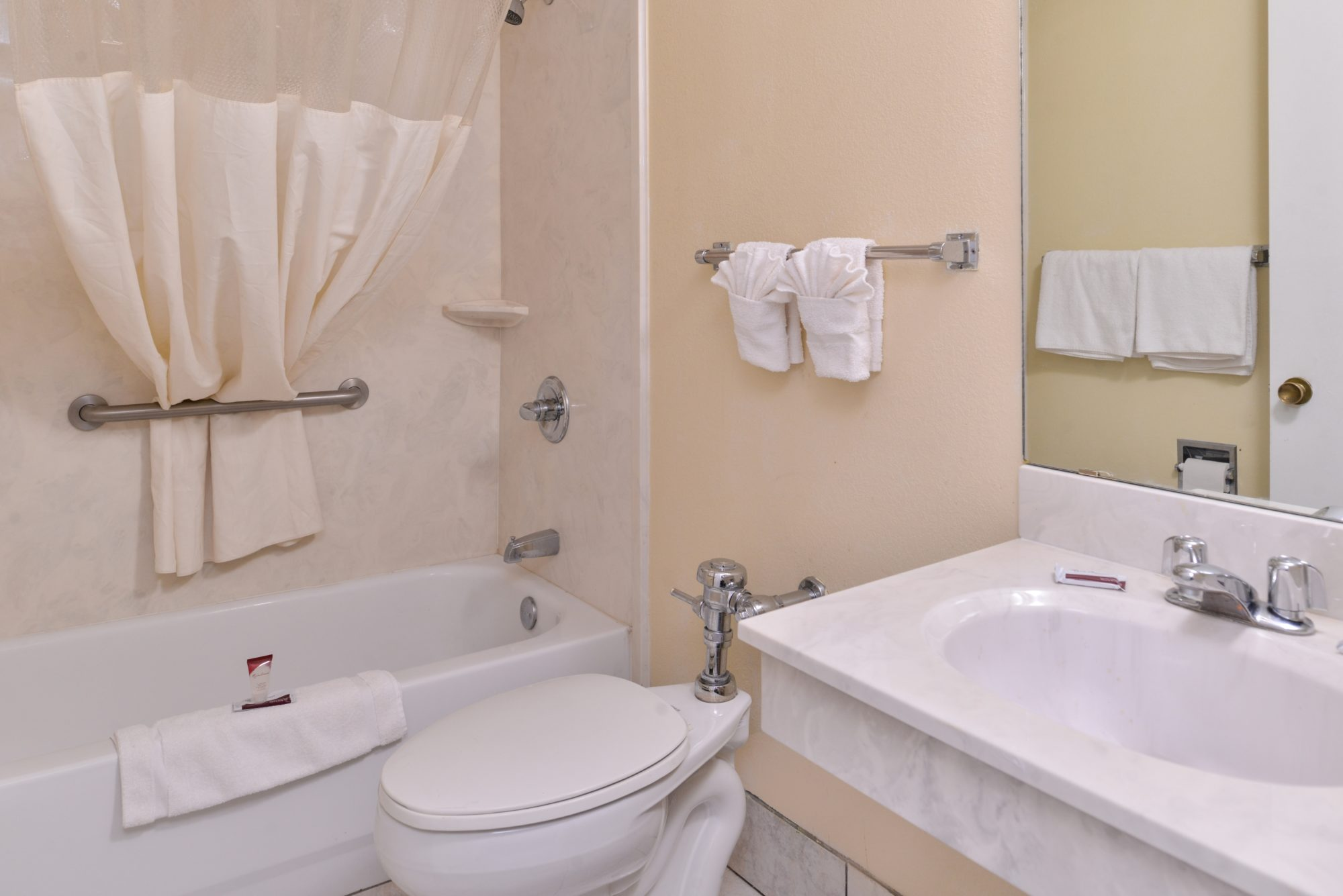 Shower tub, shower curtain, towel rail with towels, toilet, vanity unit, mirror