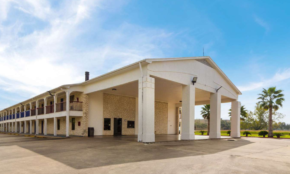 Two story building, exterior room entrances, covered walkways, hotel entrance with canopied drive through