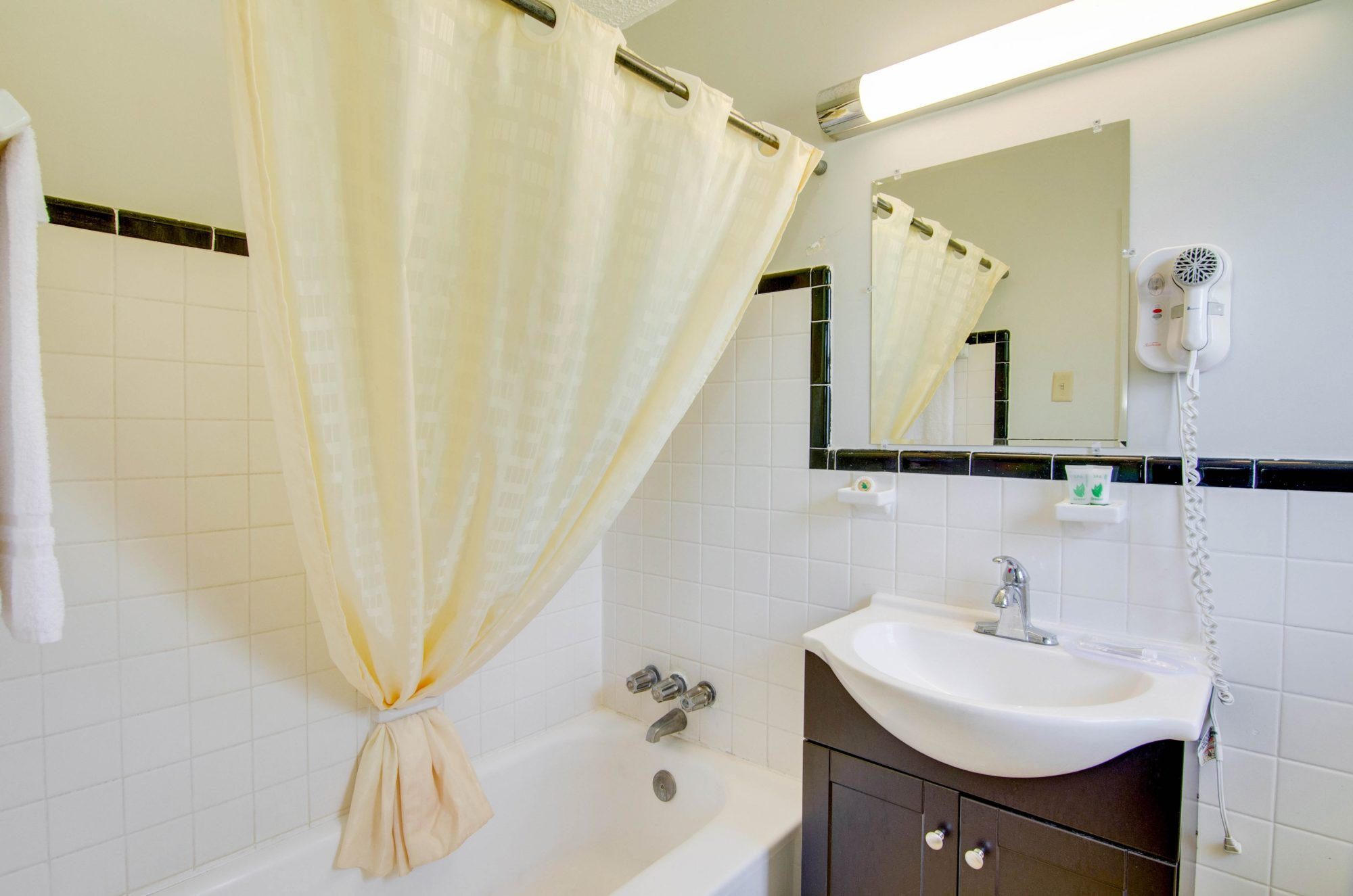 Shower tub with shower curtain, towel rail with towel, vanity unit, wall mounted hair dryer and mirror with overhead strip light