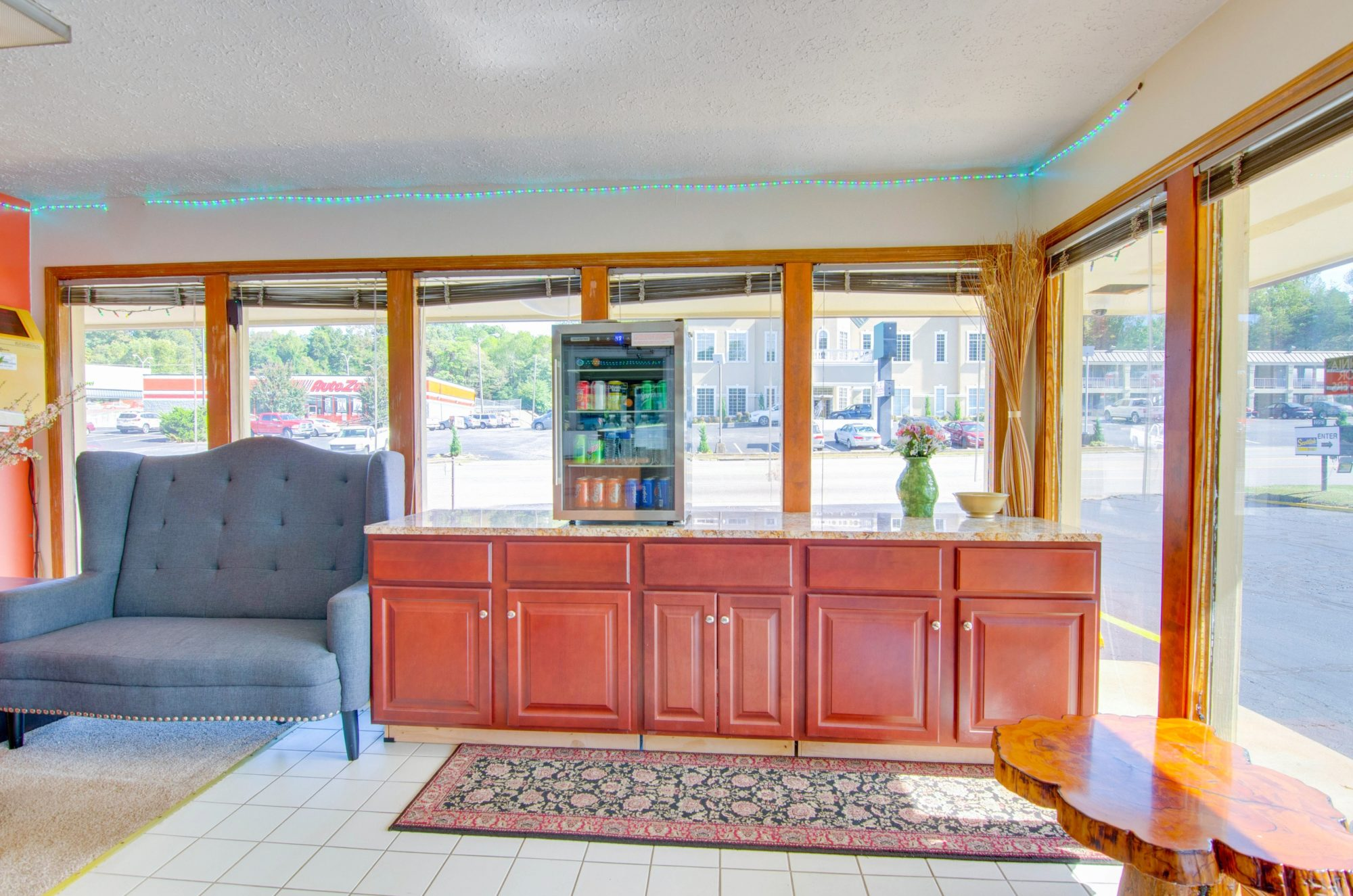 Sofa, counter with chilled soft drinks, small occasional table, tiled flooring with rug