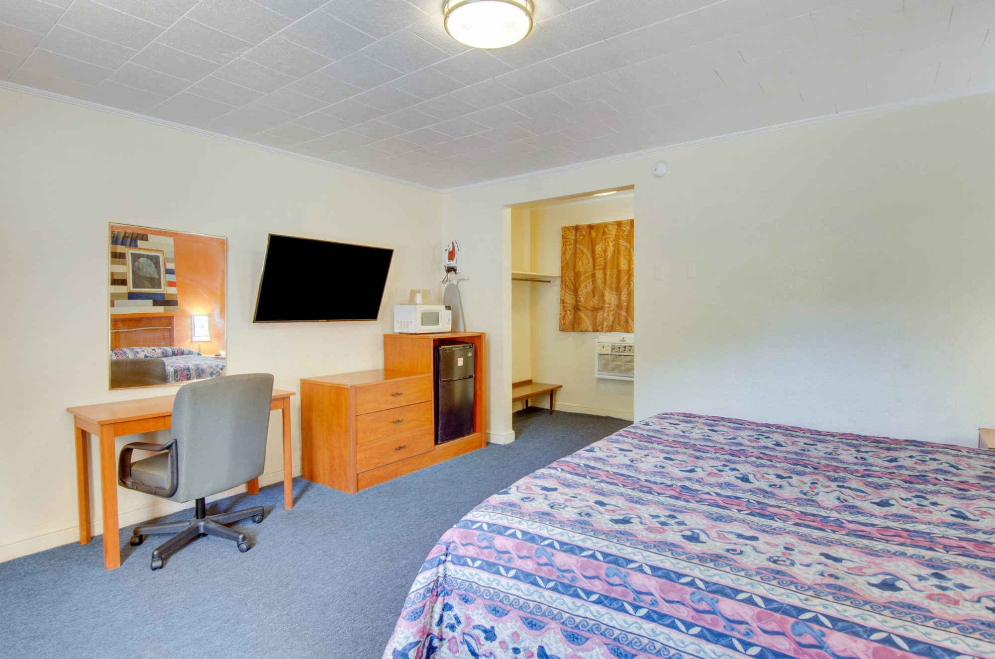 King bed, desk and office chair, wall mounted mirror, flat screen tv and ironing board and iron, wooden drawer unit with fridge and microwave, alcove with hanging rail and shelf, carpet flooring