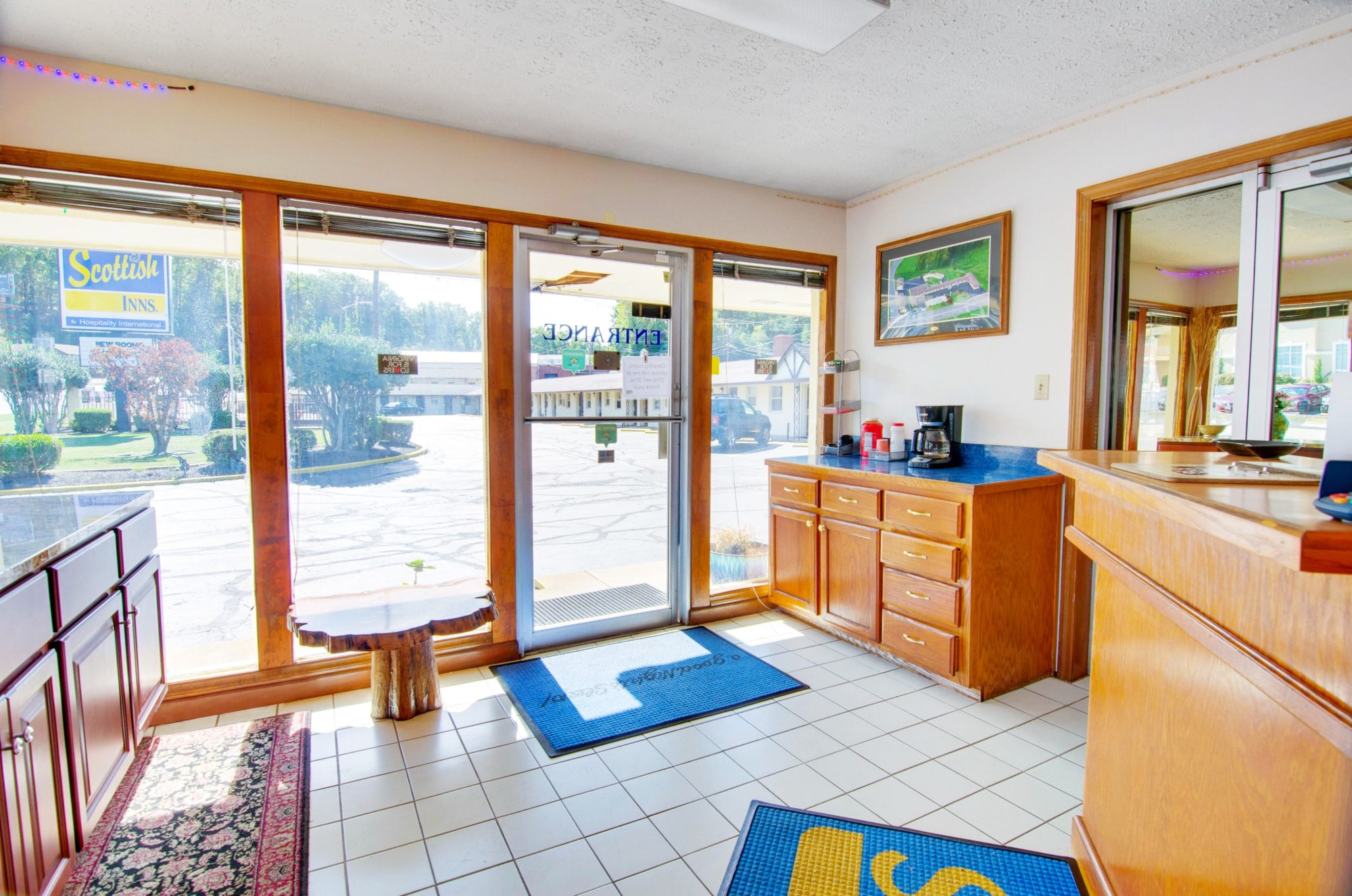 Guest check in desk , counter with coffee pot, occasional talbe, tiled flooring with rug