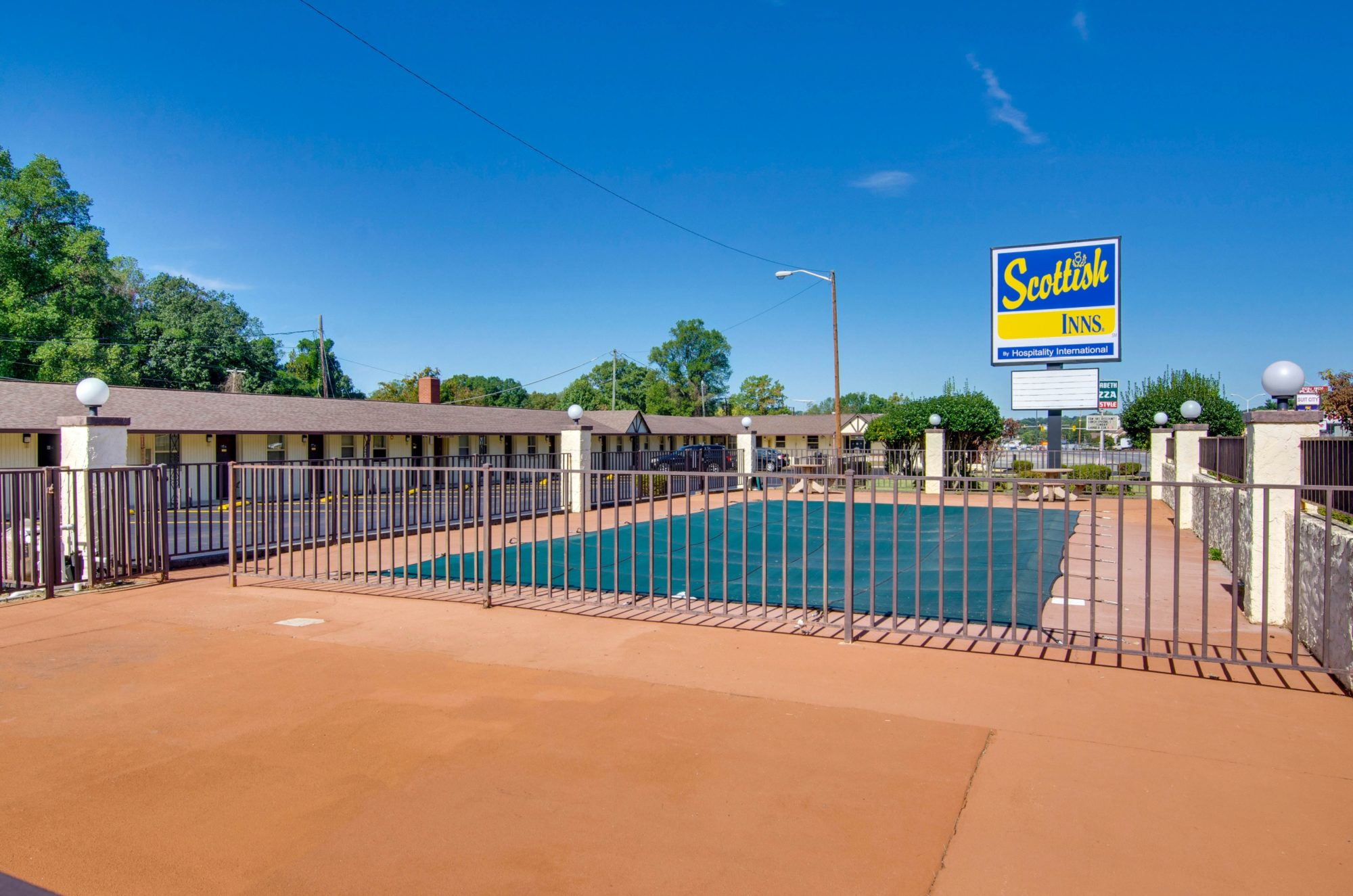 Exterior pool with safety fencing, brand signage, one story hotel building with exterior room entrances and parking spaces